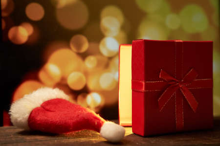 New year's red gift with a bow on a brown wooden table on a gold bokeh background with a copy space Stock fotó