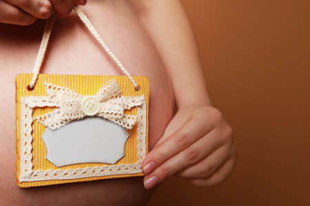A pregnant woman holds an empty handmade sign next to her belly on a yellow background