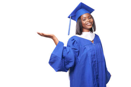 African-American beautiful woman in a blue robe and hat, on a white isolated background smiles and shows something