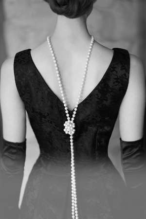 Beautiful female figure from the back in a black dress and pearls in the style of 20-30 years of the XX century. Black and white photo Standard-Bild