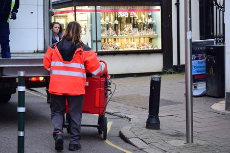 English postal lady pushing post truck in Barnstaple, Devon