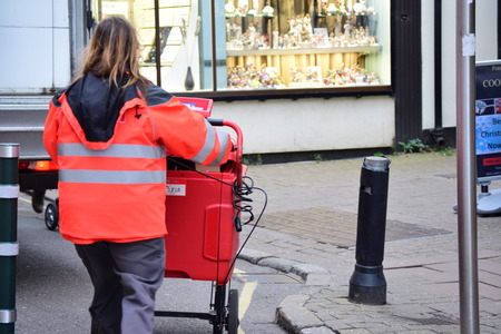 addressed: English postal lady pushing post truck in Barnstaple, Devon