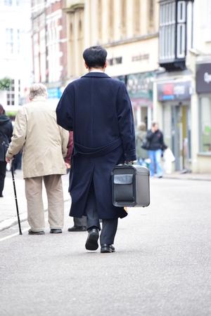windowpanes: Business man walking in Barnstaple, Devon, UK