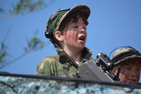 laser tag: Young Boy playing laser tag while dressed in army style overalls