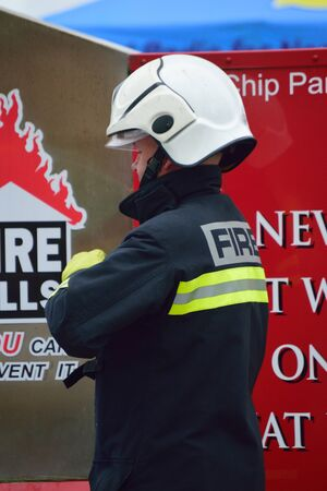 Fire officer standing near a fire kills sign in full PPE