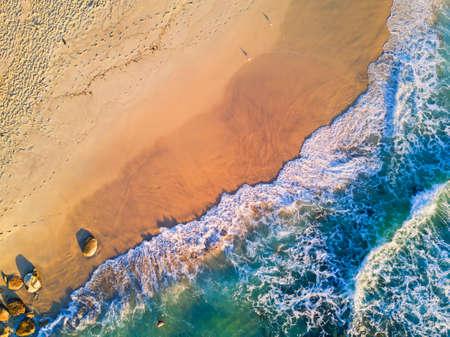 朝の航空写真ビューで澄んだ水のビーチ。