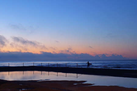 morning blue hour: A surfer going to surf in the early morning