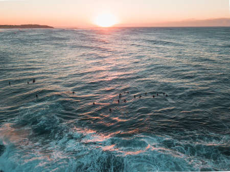 Sunrise view with surfers in the ocean.
