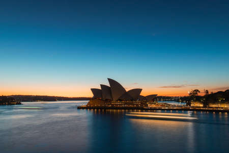 Sydney, Australia - July 19, 2018: Ferry trails in front of Sydney Opera House at dawn time.