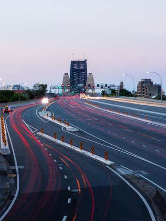 Trails of car traffic in the highway leading up to Sydney Harbour Bridge at sunset time. 免版税图像