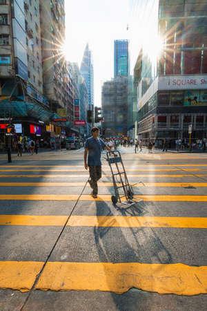 Hong Kong - 3 oktober 2019: Een man die een trolley meeneemt bij het oversteken onder het zonlicht.