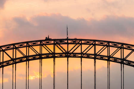 The middle arch of Sydney Harbour Bridge with orange cloudy sky.