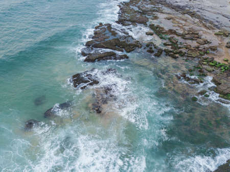 Aerial view of rocky coastline and blue water.