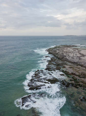 Aerial view of rocky coastline with cloudy sky. Stock Photo