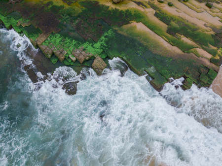 Wave water around mossy rocks on the coastline.