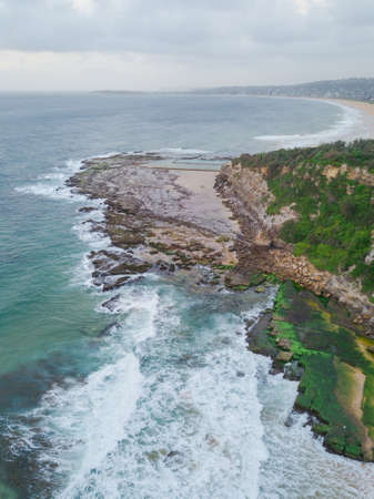 Aerial view of rocky coastline and Narrabeen headland in the morning.