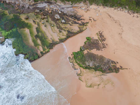 Aerial view of mossy rocks on the coastline.
