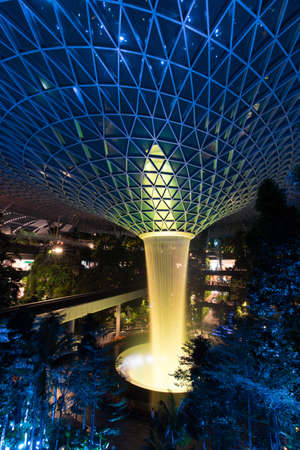 Singapore - February 6, 2020: Yellow lights up on the garden and rain vortex at Jewel Changi Airport. Editorial
