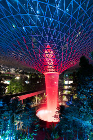 Singapore - February 6, 2020: Red lights up on the garden and rain vortex at Jewel Changi Airport. Editorial