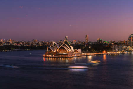 Sydney, Australia - March 20, 2020: Boat trails in front of Sydney Opera House at night. Editorial