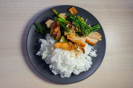 Stir fried crispy pork belly and broccolini with rice. Stock Photo