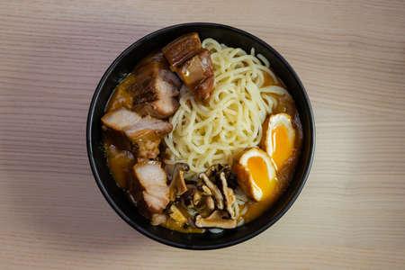 A bowl of curry ramen with pork, egg, and mushroom.