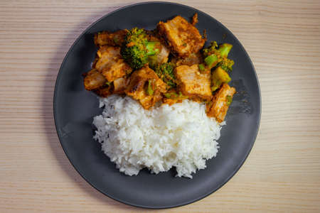 A plate of pad prik khing, thai red curry stir fried, with pork belly and white rice. Stock Photo
