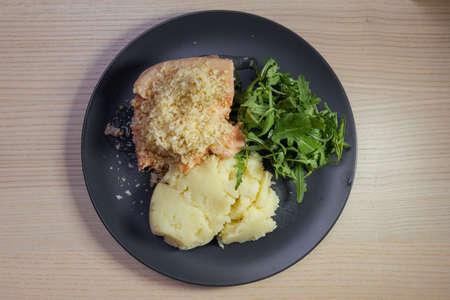 A plate of salmon, rocket salad, and mashed potato.