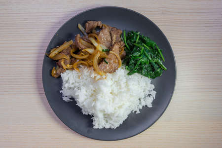 A plate of grilled beef, sautéed spinach, and white rice. Stock Photo