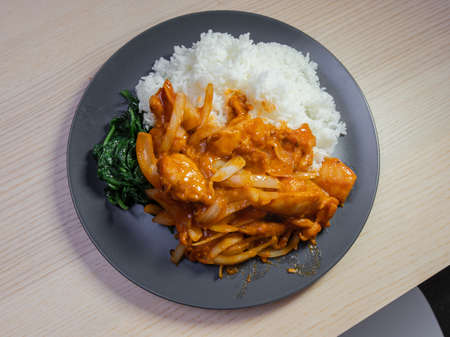 A plate of spicy chicken and rice.