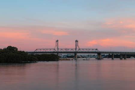 Ryde Bridge over Parramatta River with pink sunset sky.