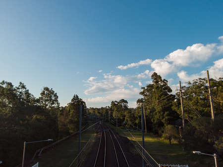 Empty railway surrounded by trees and blue sky.