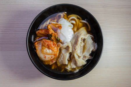 A bowl of udon with pork, egg, and kimchi.