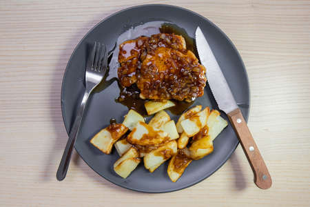A plate of pork steak and potato with brown sauce. Stock Photo