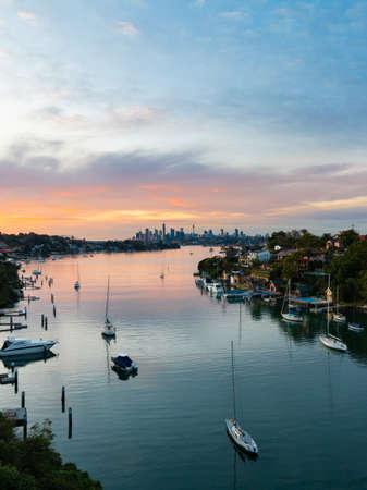 Sydney, Australia - May 20, 2020: Colorful sunrise view over Sydney skyline along Parramatta River. Editorial