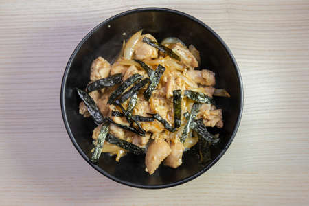 A bowl of oyakodon, chicken and egg on rice with nori seaweed on top. Stock Photo