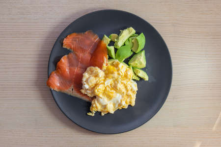 A plate of smoked salmon, scrambled eggs, and avocado.