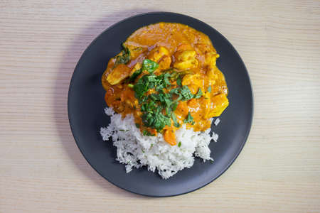 A plate of steam rice with chicken curry.