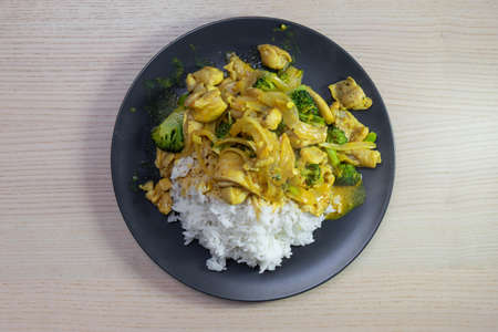 A plate of yellow chicken curry with steam rice.