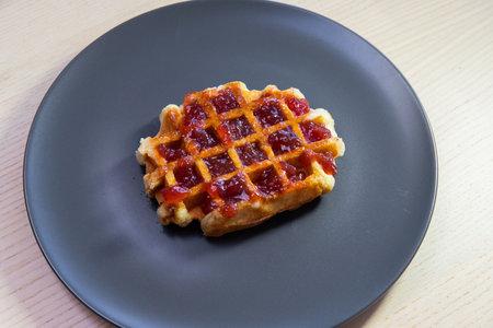 A piece of waffle with strawberry jam. Standard-Bild