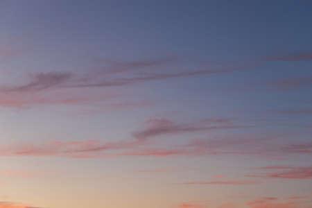 Wispy clouds on clear sunrise sky.