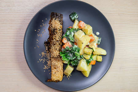 A plate of salmon with roasted vegetables.