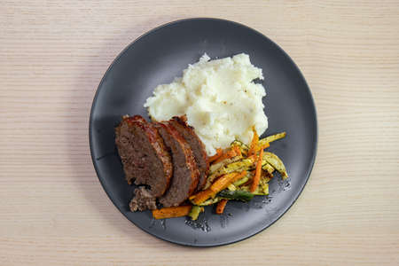 A plate of meatloaf with mashed potato and vegetables. Standard-Bild