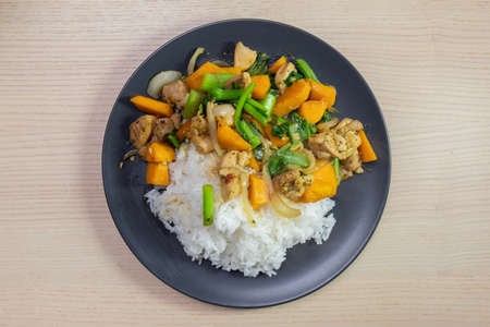 A plate of chicken and vegetable stir-fry with steam rice.