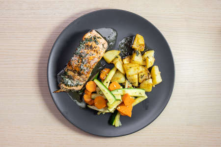 A plate of grilled salmon with potato and vegetables.