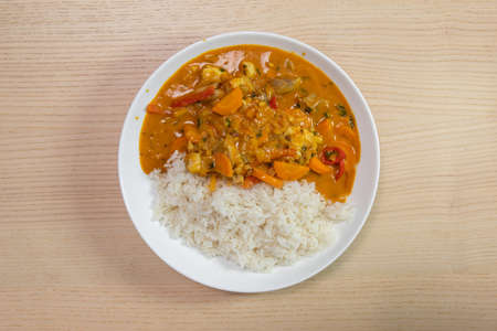 A plate of rice with chicken and vegetable curry.