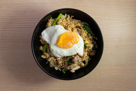 A bowl of fried rice with fried egg on top.