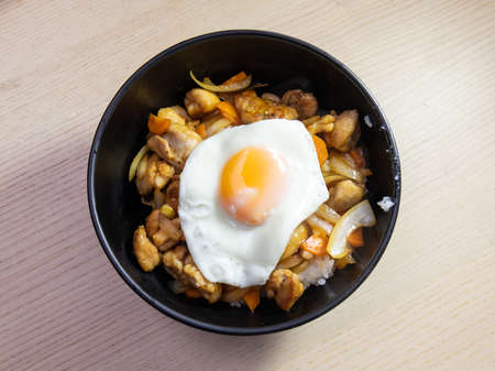 A bowl of teriyaki chicken with fried egg on top. Standard-Bild
