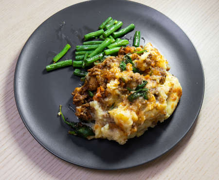 A plate of beef and potato pie with green beans on the side. Standard-Bild