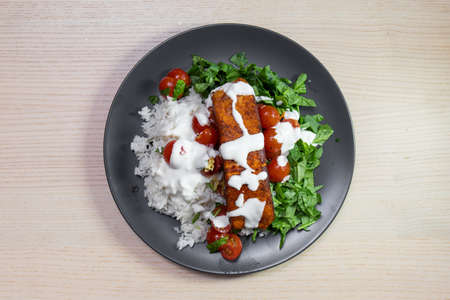 Grilled salmon topped with white sauce served with rice and green salad. Standard-Bild
